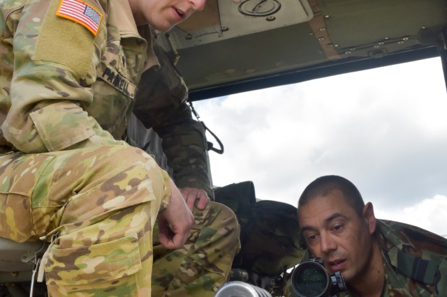 Spc. Joseph Parnell, a 15T Black Hawk mechanic with 3rd Battalion, 227th Aviation Regiment, 1st Air Cavalry Brigade, and a member of the Bulgarian special forces discuss placement options for employing a Blaser R93 Tactical sniper on a UH-60 Black Hawk helicopter.