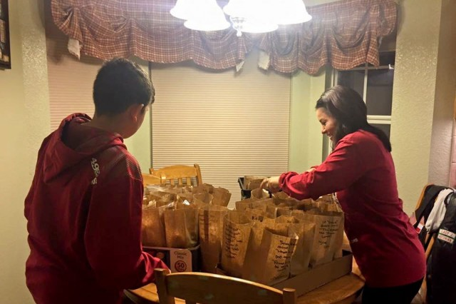 Andre Figueroa, left, helps a family friend pack lunches for a local homeless shelter earlier this year.