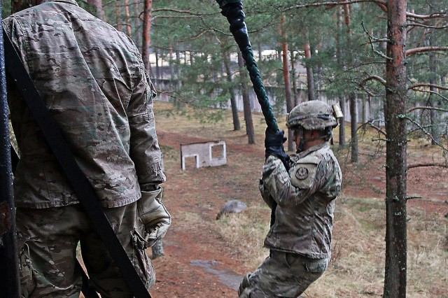 A Soldier assigned to Headquarters and Headquarters Troop, 3rd Squadron, 2nd Cavalry Regiment, slides down a rope from a tower during multinational fast rope familiarization training, April 20, at Adazi Military Base, Latvia. American soldiers in the region supporting Operation Atlantic Resolve joined allies from Latvia, Canada, Lithuania and Germany for the annual training event.