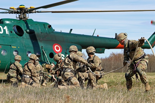 Soldiers assigned to Headquarters and Headquarters Troop, 3rd Squadron, 2nd Cavalry Regiment, connect themselves to a rope connected to a Latvian Mi-17 helicopter during special purpose insertion extraction training, April 21, at Lielvarde Air Base, Latvia. Allies from Latvia, Canada, Lithuania and Germany participated in the event, which included cold and hot load training on UH-60 Blackhawk helicopters and fast rope insertion extraction exercises.