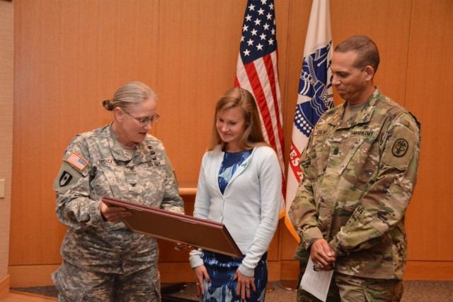 Army Col. Jennifer Bedick, Brooke Army Medical Center chief nursing officer, and BAMC Command Sgt. Maj. Albert Crews present Monika Korra (center) a token of appreciation for speaking at the Sexual Assault Awareness and Prevention Month event April 15 in the San Antonio Military Medical Center auditorium.
