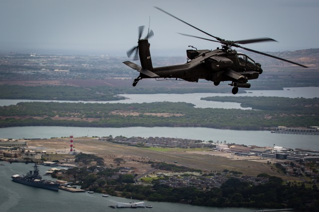 An AH-64D Apache from 2-6 Cavalry Squadron, 25th Combat Aviation brigade, flies above the USS Arizona Memorial and the USS Battleship Missouri Memorial in Pearl Harbor en route to Wheeler Army Airfield, April 24. The Apaches were reassigned to the 25th Combat Aviation Brigade from National Guard units as part of U.S. Army Aviation restructuring.
