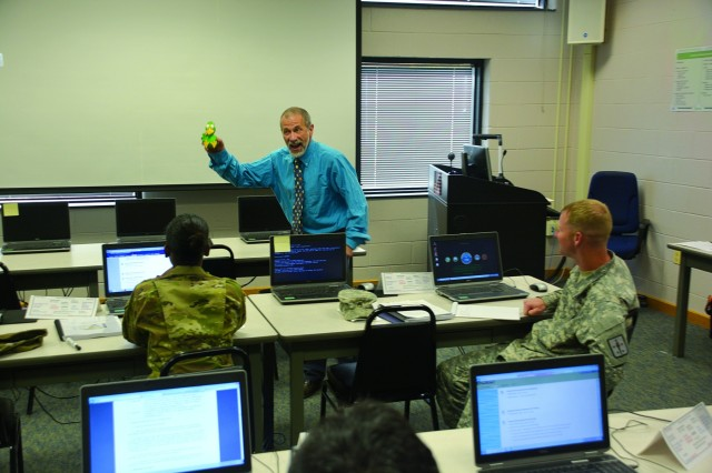 Keith Ferguson, a staff and faculty instructor at the Army Logistics University, attempts to entertain his class while acting like a clown with his Mr. Squeakers prop to introduce them to the design concept of their Systems Approach to Training class. (Photo by Amy Perry, Fort Lee Public Affairs)