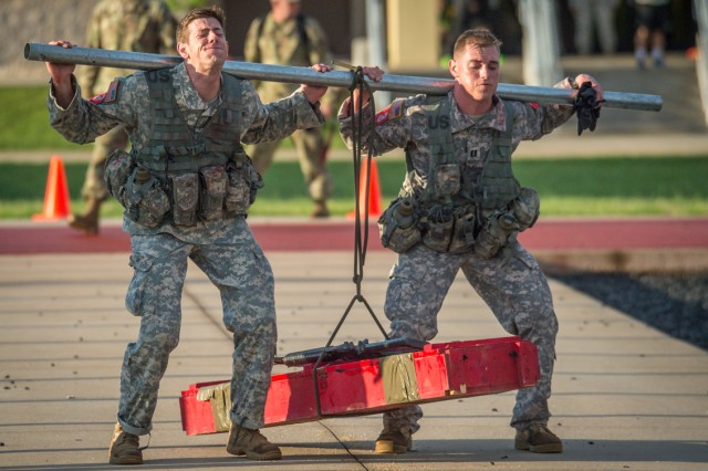Capt. Gregory Shepard and 1st Lt. Christopher Price, representing 70th Brigade Engr. Bn., Fort Wainwright, Alaska, conducts a bangalore carry at the first stop during the X-Mile Run April 21.