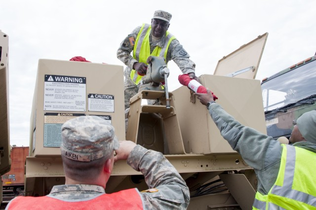 A National Guard Soldier passes out cloths used to help Soldiers check engine oil levels during Operation Patriot Bandoleer at Military Ocean Terminal Sunny Point, North Carolina, April 14.