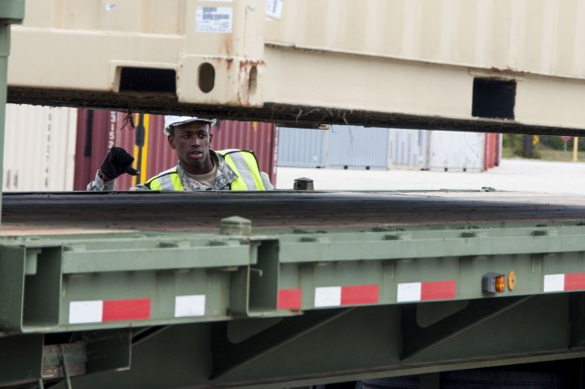 An Army Reserve Soldier directs a Mi-Jack operator from the ground while they load a truck with cargo during Operation Patriot Bandoleer at Military Ocean Terminal Sunny Point, North Carolina, April 14.