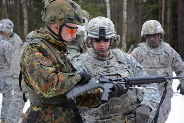 Maj. Gen. Walt Piatt, director of Operations, Readiness and Mobilization, Army G-3/5/7, said Soldiers in Korea and Europe get full-spectrum training all the time. Here, Staff Sgt. James Callahan, platoon sergeant, Charlie Company, 44th Expeditionary Signal Battalion, inspects a M16 used by a German Soldier with 383rd Communications and Information Systems Battalion prior to entering the firing range Feb 19, 2015 at the Grafenwoehr Training Area.