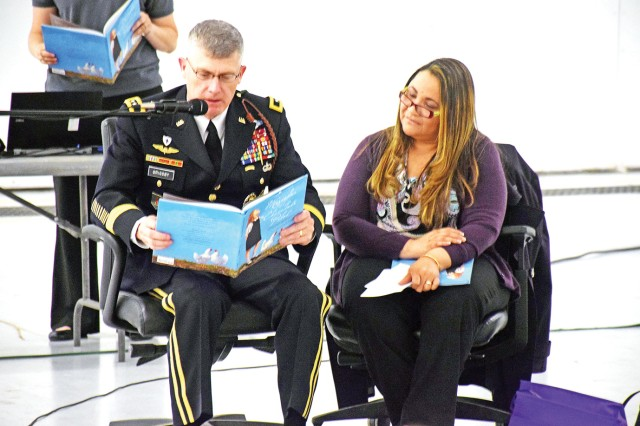 Maj. Gen. Wayne W. Grigsby Jr., commanding general of the 1st Infantry Division and Fort Riley, and his wife Cynthia, read to military children during the Military Child Education Coalition's Tell Me a Story event at Marshall Army Airfield, Fort Riley, Kansas.