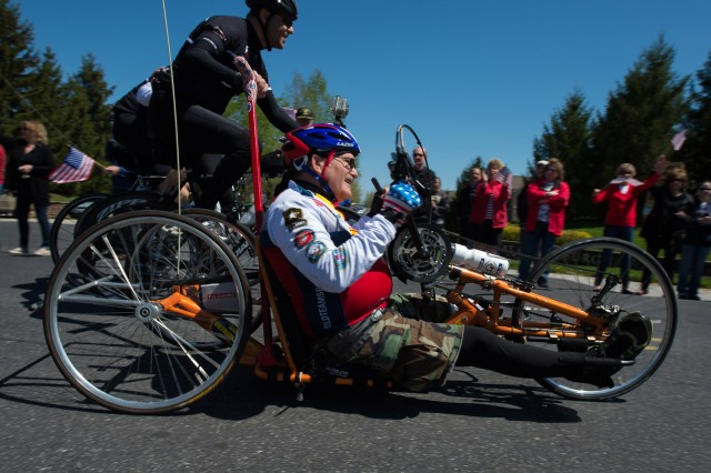Vietnam War Army veteran Bill Czyzewski rides a recumbent bicycle to the applause of a crowd in Gettysburg, Pa., April 24, 2016. More than 150 disabled veteran cyclists were paired amongst 600 able-bodied cyclists to ride 110 miles from Arlington, Va., to Gettysburg over two days in honor of veterans and military members.