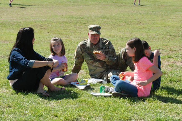 1st. Sgt. Matthew Halstead sits in the grass with his family as they eat on April 22 at Rowe Field, Fort Sill, during the 75th Field Artillery Brigade's Month of the Military Child celebration. The event was free and open to service members and their families.