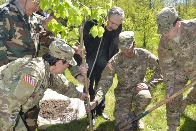 """U.S. Army civil affairs Soldiers along with Soldiers with the Joint Multinational Training Group-Ukraine and Ukrainian locals plant a """"peace tree"""" Apr. 28, 2016, at the National Park Headquarters in Ivano-Frankove, Ukraine. The tree planted was a linden tree, which traditionally is symbolic for long life and good health in demonstration of the strong bond that JMTG-U has with the local community. (U.S. Army photo by Staff Sgt. Adriana M. Diaz-Brown, 10th Press Camp Headquarters)"""