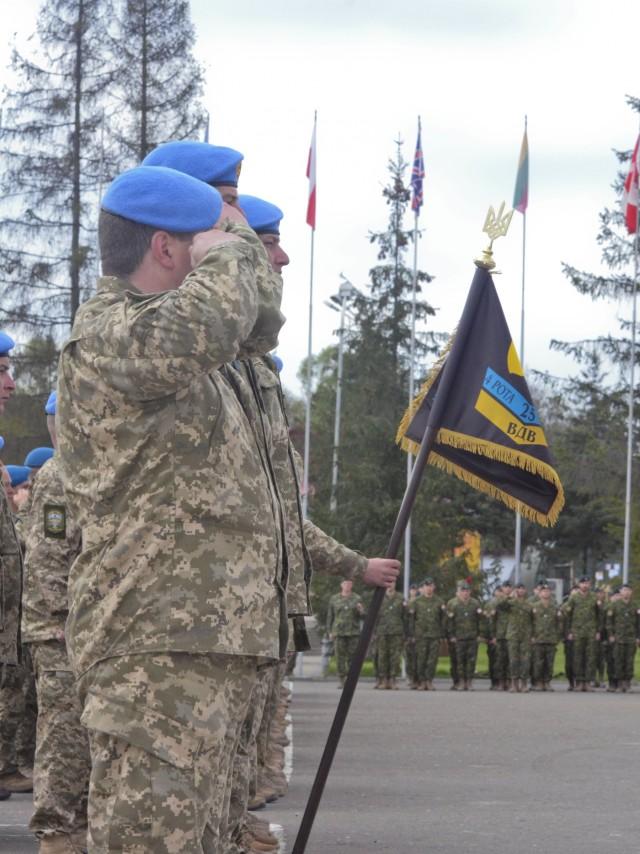 Ukrainian Soldiers salute during a JMTG-U graduation ceremony