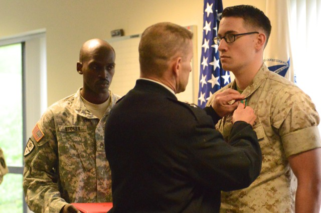 Maj. Gen. Bradley A. Becker, commanding general, U.S. Army Military District of Washington, presents an award to a Marine at the consolidated Tax Center on Joint Base Myer-Henderson Hall, Virginia, April 28, 2016. The service members and civilians who worked at the tax center this season saved patrons more than $700,000 in tax preparation fees.