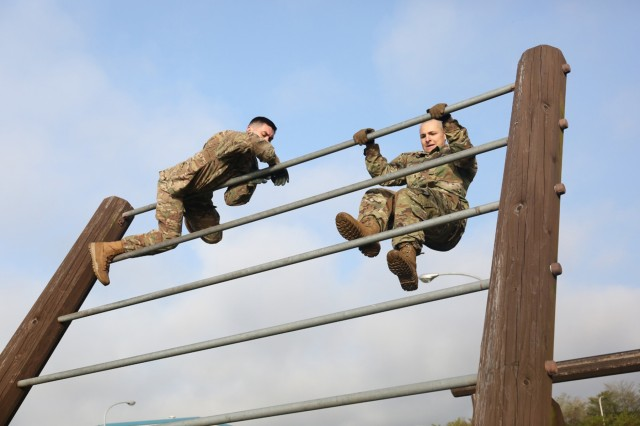 Sgt. Drew Ayers, NCO in charge of Provost Marshall Office operations and assigned to USAG Japan; left, and Spc. Lucas Patron, wheel vehicle mechanic assigned to I Corps Forward; right, compete in the obstacle course held April 26 at Camp Fuji, Japan for the USARJ 2016 Warrior Challenge Competition. (U.S. Army photo by Lance D. Davis)