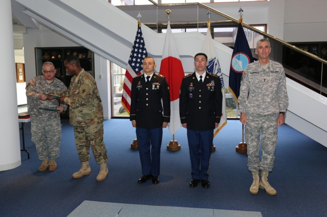 Spc. Lucas Patron, wheel vehicle mechanic assigned to I Corps Forward; left, and Sgt. Drew Ayers, NCO in charge of Provost Marshall Office operations and assigned to USAG Japan; center, stand with Maj. Gen. James F. Pasquarette, USARJ commanding general, to receive their awards for winning the USARJ Warrior Challenge. (Photo by Lance D. Davis)
