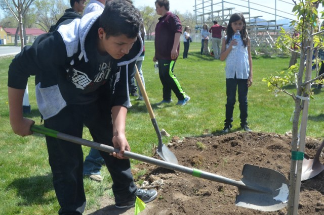 One last high school student finishes filling the hole around a tree planted near the Ballpark memorial April 21 at an Earth Day event at U.S. Army Dugway Proving Ground, Utah. Photo by Bonnie A. Robinson, Dugway Public Affairs.