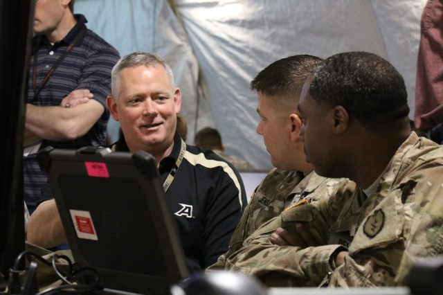 CERDEC's Dr. Michael Brownfield talks with Soldiers from the 25th Infantry Division out of Hawaii during U.S. Army's Cyber Blitz April 2016 at Joint Base McGuire-Dix-Lakehurst, N.J. Cyber Blitz provides the Army a venue to observe and assess cyber and electromagnetic activity-related interactions in a Tactical Command Post. (U.S. Army CERDEC photo by Kristen Kushiyama)