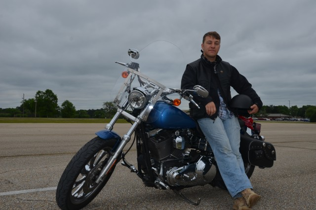 Spc. Scott Burns poses with is 2007 Harley Davidson Dyna Low Rider. Last fall, Burns, and his wife Samantha, were involved in a motorcycle accident and Burns attributes the Motorcycle Safety Foundation's Basic RiderCourse training to saving their lives. U.S. Army photo by Taryn Gillespie
