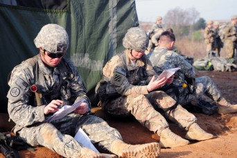 Staff Sgt. Zachery Holder (left), 210th Fires Brigade, and Sgt. Mea Jenkins, Brian Allgood Army Community Hospital, conduct a final review of study material before participating in Expert Field Medical Badge testing near Panmunjeom, South Korea Apr. 25, 2016.