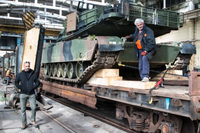 Rail workers guide a railcar carrying a M1A2 Main Battle Tank into a warehouse during a port operation May 1, 2015 at the Port of Varna, Bulgaria. During the operation, workers changed the trucks of railcars carrying equipment scheduled to be used by Soldiers of the 1st Battalion, 64th Armor Regiment, 1st Armored Brigade Combat Team, 3rd Infantry Division during Exercise Noble Partner May 11-26 at Vaziani, Georgia. (U.S. Army photo by Staff Sgt. Michael Behlin)