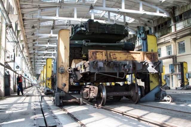 Workers raise a railcar carrying a M1A2 Main Battle Tank in order to change the railcar trucks during a port operation May 1, 2015 at the Port of Varna, Bulgaria. The adjustment by rail workers will allow the smooth transition of equipment from NATO countries using European-spec rails to those designed during the Soviet-era. (U.S. Army photo by Staff Sgt. Michael Behlin)