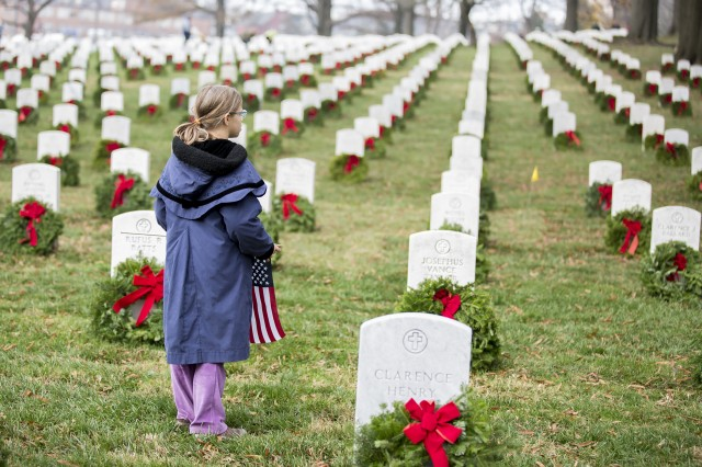 Holding an American flag, a young girl — one of thousands of volunteers — stares before helping place wreaths on tombstones at Arlington National Cemetery Dec. 12, 2015, as part of the annual Wreaths Across America initiative. Army and cemetery officials hosted a public open house April 27 to brief the community and stakeholders on details of a cemetery expansion project, which could add as many as 25,000 grave sites to a plot of land near the Air Force Memorial, contiguous to the current cemetery's border.