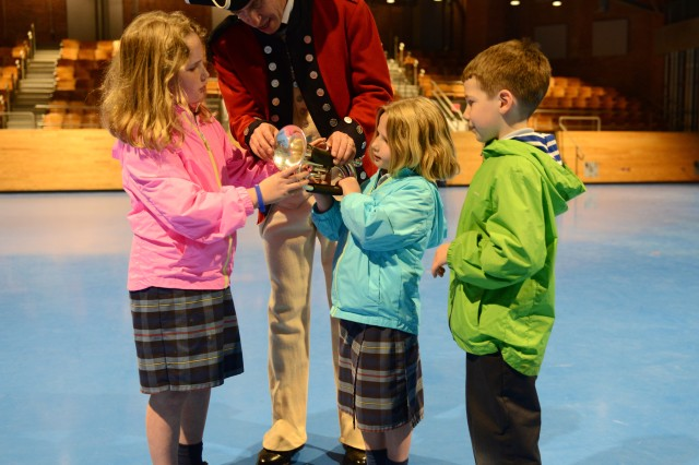 A Soldier from the 3rd U.S. Infantry Regiment (The Old Guard) Fife and Drum Corps helps a young audience member play a bugle after the kick-off performance of Twilight Tattoo May 4, 2016 on Joint Base Myer-Henderson Hall. Twilight Tattoo is a free, one-hour military history show performed all summer long on Joint Base Myer-Henderson Hall, Virginia.