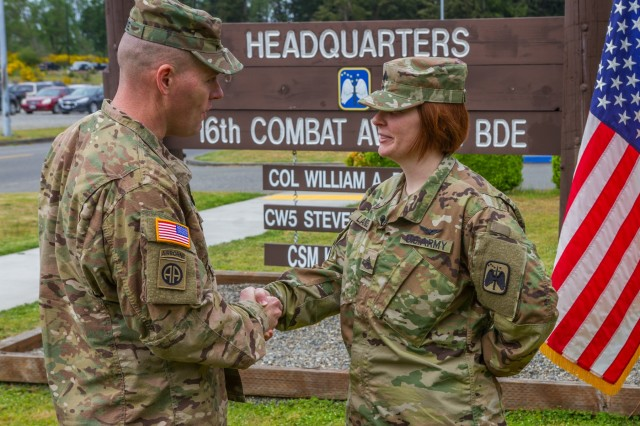 U.S. Army Sgt. Kayci Landes, an attack helicopter repairer assigned to 16th Combat Aviation Brigade, 7th Infantry Division, I Corps, is congratulated by Command Sgt. Maj. Jack H. Love, 7th ID command sergeant major, following a re-enlistment ceremony at Joint Base Lewis-McChord, Wash., May 4. Landes became the first female Soldier to re-enlist in the Army as military occupational specialty 19D, cavalry scout.