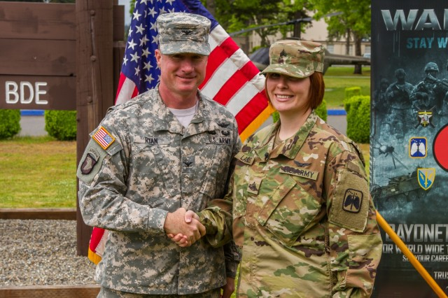 U.S. Army Sgt. Kayci Landes, an attack helicopter repairer assigned to 16th Combat Aviation Brigade, 7th Infantry Division, I Corps, is congratulated by Col. William A. Ryan, 16th CAB commander, following a re-enlistment ceremony at Joint Base Lewis-McChord, Wash., May 4. Landes became the first female Soldier to re-enlist in the Army as military occupational specialty 19D, cavalry scout.