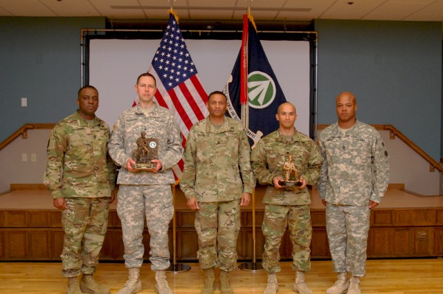 SDDC Senior Enlisted Leader Cmd. Sgt. Maj. Kevin McKeller (center) presents U.S. Army Sgt. Maksym Moskalenko (second from left), 598th Transportation Brigade, and Spec. Mitchell Keeton (second from right), 597th Transportation Brigade, with their trophies for SDDC NCO and Soldier of the Year respectively. 598th Cmd. Sgt. Maj. Gussie Bellinger and 597th Cmd. Sgt. Maj. Jerome Smalls (right) appear with their Soldiers during the awards ceremony.