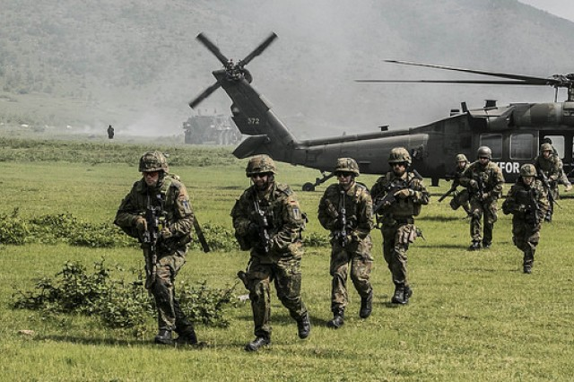 German soldiers operating under Multinational Battle Group-East conduct an air infiltration exercise as part of a larger two-day operation deemed Operation Sharp Griffin, May 6, on Orahovac Range in Kosovo. During day one of the two day event, the German contingent perfected their joint maneuver and air assault techniques.