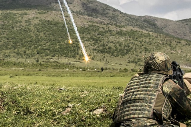 A German soldier serving with the Multinational Battle Group-East and Kosovo Force, watches as a flare illuminates a set of simulated targets during Operation Sharp Griffin May 6, at Orahovac Range in Kosovo.