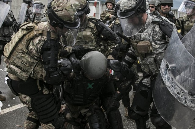 U.S. Army Soldiers assigned to Multinational Battle Group-East apprehend a group of simulated protestors May 7, during Operation Sharp Griffin held on Camp Prizren, Kosovo. The operation was part of a 36-hour operational readiness exercise which tested the military decision making process and reaction capabilities of the German Armed Forces stationed in Kosovo.