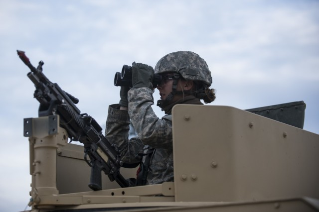 Pvt. Ashley Crager, a U.S. Army Reserve military police Soldier from Tempe, Arizona, with the 56th Military Police Company (Combat Support), of Mesa, Arizona, looks through a pair of binoculars before a cordon and search training lane at Fort Hunter-Liggett, Calif., May 4.