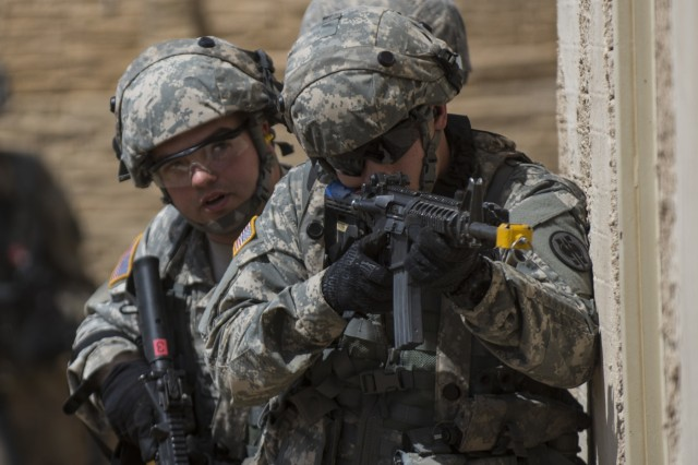 A team of U.S. Army Reserve military police Soldiers from the 56th Military Police Company (Combat Support), of Mesa, Arizona, prepare to clear a building in a makeshift village during a cordon and search training lane at Fort Hunter-Liggett, Calif., May 4.
