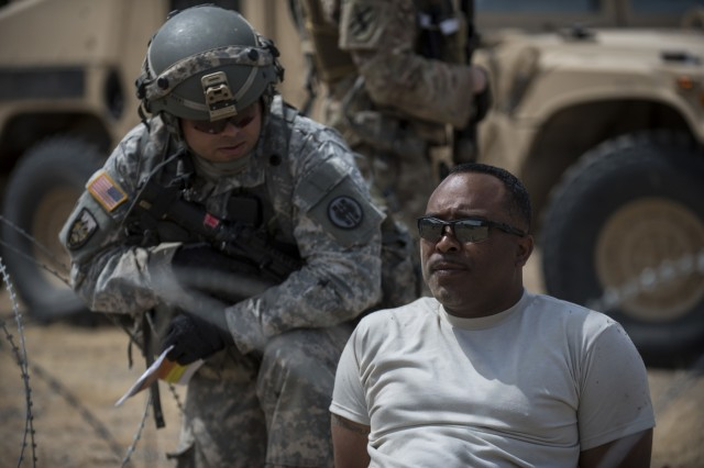 Sgt. 1st Class Malcolm Russell, a U.S. Army Reserve observer-coach trainer with the 91st Training Division, of Camp Parks, California, plays the role of a high-value target during a cordon and search training lane conducted by a platoon from the 56th Military Police Company (Combat Support), of Mesa, Arizona, at Fort Hunter-Liggett, Calif., May 4.