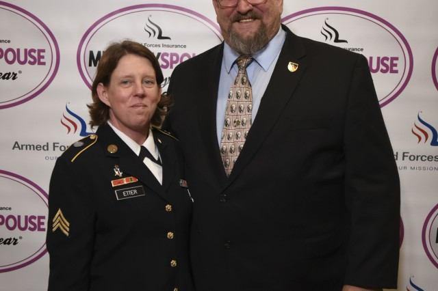 Army Spouse of the Year Dave Etter stands on stage May 5, 2016, next to his wife, Sgt. Stephanie Etter, a respiratory therapist at Landstuhl Regional Medical Center in Germany. Etter was recognized at a luncheon at the Fort Myer Officers Club, Joint Base Myer-Henderson Hall, Va .  (Reprinted here and on any military publication with permission of AP Images.)