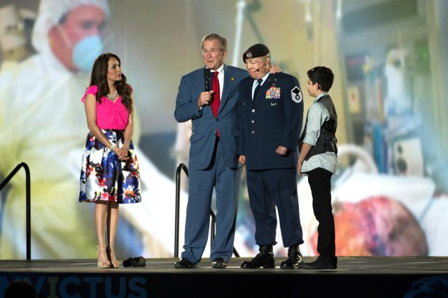 Former President George W. Bush stands on stage with Air Force Master Sgt. Israel Del Toro and his family during the opening ceremony to the 2016 Invictus games in Orlando, Fla. May 8, 2016. In the background is a photo of Bush visiting Del Toro in the hospital.