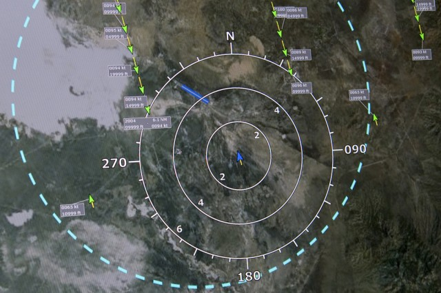 How the Ground Based Sense And Avoid system appears onscreen, to the unmanned vehicle operator. The blue outer ring is the Operational Volume, a buffer. Within it are three rings indicating 6, 4 and 2 miles from the operator's unmanned craft at the center (blue arrow). The green dashed lines ending in arrows are other approaching aircraft. An Alert Display next to this screen lists prioritized warnings for the operator. Photo by Al Vogel / Dugway Public Affairs