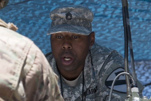 Sgt. 1st Class Denell Simmons, an infantryman assigned to Headquarters and Headquarters Company, 3rd Battalion, 8th Cavalry Regiment, 3rd Armored Brigade  Combat Team, 1st Cavalry Division, provides instruction to Spc. Sam Mewes of the 52nd Infantry Regiment, during the Call for Fire station at the Expert Infantryman Badge training and testing at Fort Hood, Texas, May 3. More than 700 Soldiers from the 1st Cavalry Division, as well as some from Fort Carson and Fort Polk underwent two weeks of training and one week of testing in basic infantry skills to earn the EIB at Fort Hood, Texas, from April 25 to May 13.