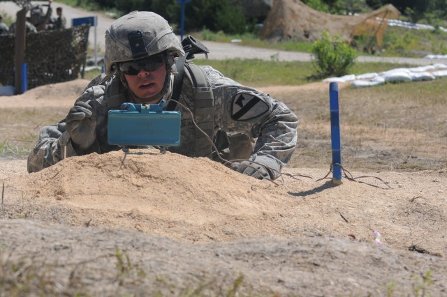1st Lt. Skyler Reynolds, an infantry officer assigned to 215th Brigade Support Battalion, 3rd Armored Brigade Combat Team, 1st Cavalry Division, places a simulated Claymore mine May 6 at the Expert Infantryman Badge training site at Fort Hood, Texas. Reynolds was training in preparation of EIB testing May 9 through 13.