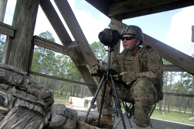 Spc. John Heard, an infantryman with Troop C, 6th Squadron, 8th Cavalry Regiment, 2nd Infantry Brigade Combat Team, 3rd Infantry Division, spots targets for Soldiers while they shoot sniper rifles during training at Fort Stewart, Ga., May 3, 2016. Spotters guide Soldiers on where to aim in order to hit targets with accuracy. (U.S. Army photo by Spc. John Onuoha / Released)