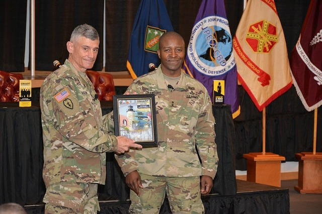 US Military Academy, West Point, Superintendent, Lt. Gen. Robert Caslen Jr. accepts a small token of appreciation from Communications-Electronics Command Commanding General and APG Senior Installation Commander,  Maj. Gen. Bruce Crawford, after Caslen delivered the keynote address to the 2016 APG SHARP Summit, May 10, in the Mallette Auditorium on Aberdeen Proving Ground.