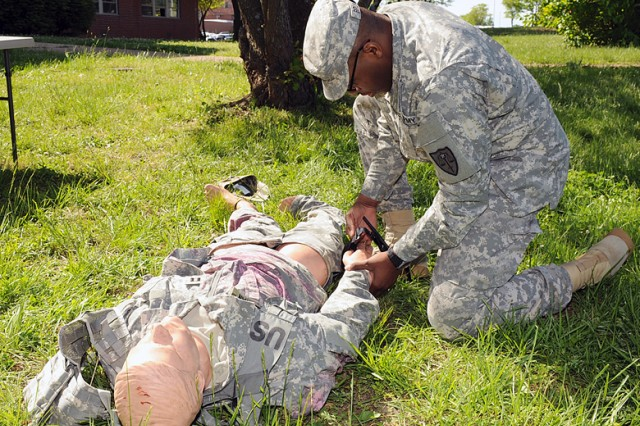 Spc. Derrick Brumfield, MSCoE and Fort Leonard Wood paralegal specialist, applies a tourniquet as part of the first aid battle-drill station.