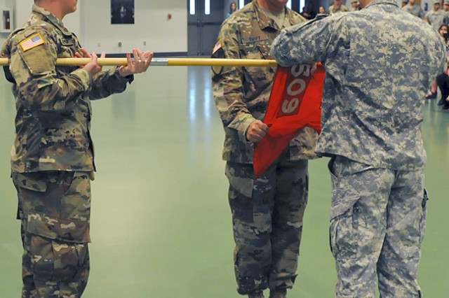 First Sgt. Jamie Swift, 509th Clearance Company first sergeant, assists Capt. Curtis Million, 509th Clearance Co. commander, in casing the company guidon in preparation for the upcoming nine-month deployment to the Republic of Korea.