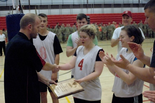 Members of the 554th Engr. Bn. volleyball team applaud as Rob Steinmacher, FMWR Sports Branch, presents the 2016 Commander's Cup Volleyball Tournament championship plaque to their coach, Allie Carrillo.