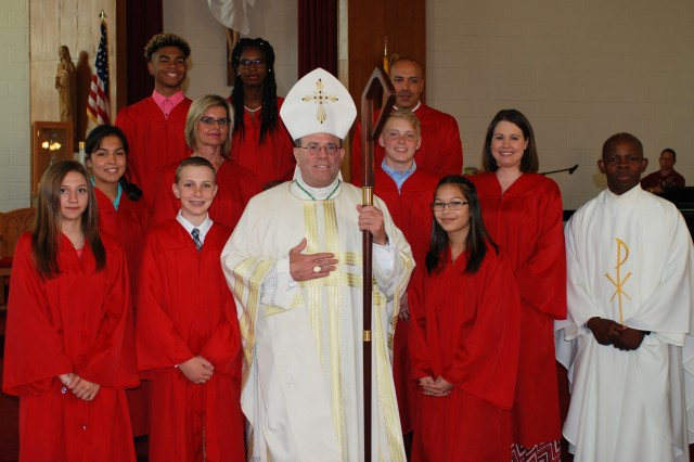 Bishop Neal Buckon, a retired Army chaplain, stands before the congregation with the prospective confirmands before the ceremony begins.Confirmation is the last sacrament of initiation into the Catholic faith.