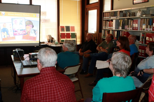Members of the Pittsburg County Genealogical and Historical Society in McAlester, Okla., listen as Brian Lott, chief of staff at McAlester Army Ammunition Plant, Okla., tells then about the importance of women in MCAAP's workforce from its early days during World War II to the present.