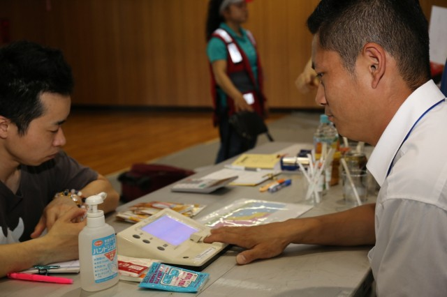 A Local National Employee measures blood pressure during the Summer Safety Day and Health Fair hosted by USAG Japan's Safety Office May 12 at the Yano Fitness Center. (U.S. Army Photos by Noriko Kudo)