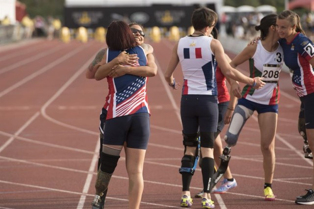 Marine Corps Lance Cpl. Sarah Rudder, U.S. Special Forces Army Staff Sgt. Lauren Montoya, France's Marion Blot, medically retired Army Sgt. Anna Manciaz, Italy's Monica Contrafatto, and Air Force Capt. Christy Wise congratulate each other after running the women's 100-meter dash during the track and field competition at the 2016 Invictus Games. (DoD photo by Roger Wollenberg)